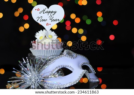 Happy New Year Eve party with cupcake and party masquerade mask on reflective table against bright color festive bokeh lights. - stock photo