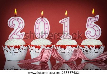 Happy New Year for 2015 red velvet cupcakes in red and white theme with lit candles on a red background, - stock photo