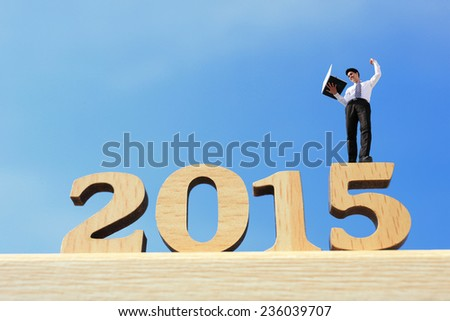 Happy new year for 2015 - success business man with laptop computer and celebrating on wood number - stock photo