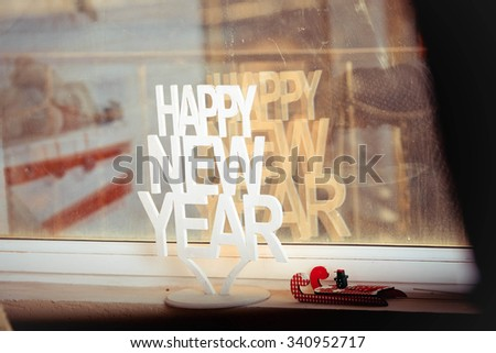 Happy New Year  greetings - text in  wood type blocks on a grunge windows background - stock photo
