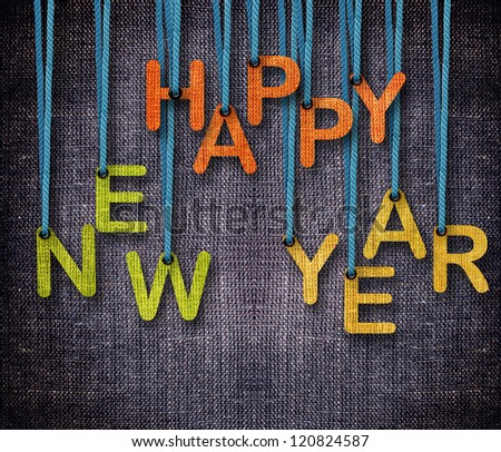 Happy New Year hanging by rope as puppeteer on sackcloth background. - stock photo