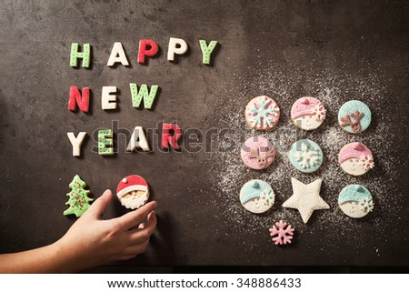 Happy new year letters with cookies in various forms. Woman's hand completes Christmas decoration.  - stock photo