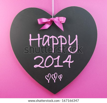 Happy New Year 2014 message greeting written on heart shape blackboard against a pink background. - stock photo