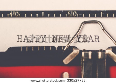 Happy New Year on old typewriter machine, hipster lifestyle holiday letter and greeting card, retro toned, selective focus  - stock photo
