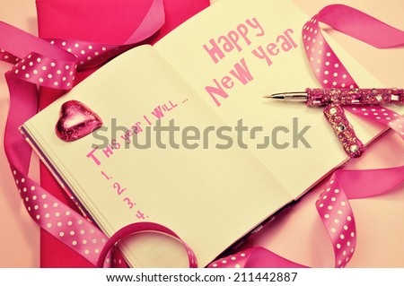 Happy New Year resolutions in diary journal book with pretty feminine pink ribbons, heart chocolate and pen with retro vintage filter. - stock photo