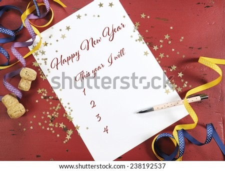 Happy New Year Resolutions planning and goal list on dark red wood background with gold stars and festive decorations. - stock photo