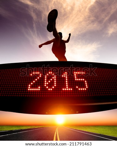 happy new year 2015.runner jumping and crossing over matrix display for celebrating 2015 - stock photo