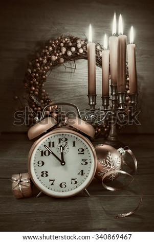 Happy New Year! Vintage alarm clock showing five to twelve on wood. This image is toned. Focus on the clock. - stock photo