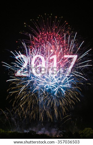 Happy New Year 2017 with colorful sparklers. The numbers 2017 are integrated into the fireworks with black background - stock photo