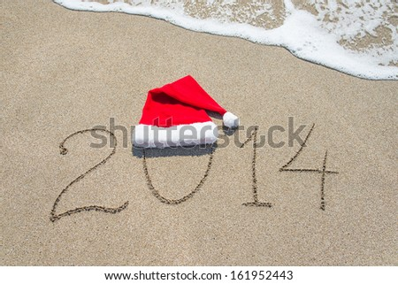 happy new year 2014 with santa hat on sea beach sand with wave - holiday concept for new years day or christmas - stock photo