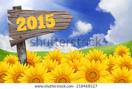 Happy New Year 2015 wooden board sign on sunflowers field - stock photo