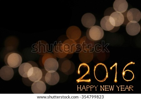 Happy New Year 2016 write by sparklers firework with defocused light blur bokeh background - stock photo