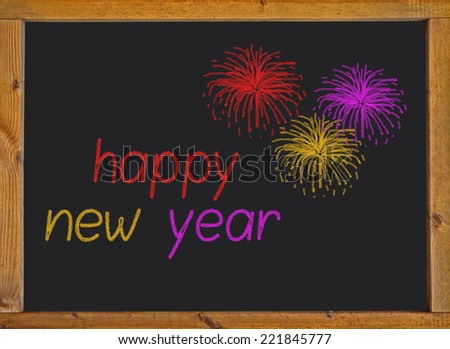Happy new year written on a small blackboard with a wooden frame - stock photo