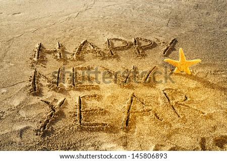 Happy New Year written on sand - stock photo