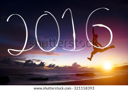 happy new year 2016.young man jumping  and drawing 2016 on beach - stock photo