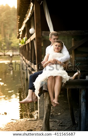 Happy newly married couple relaxing on old pier at forest - stock photo