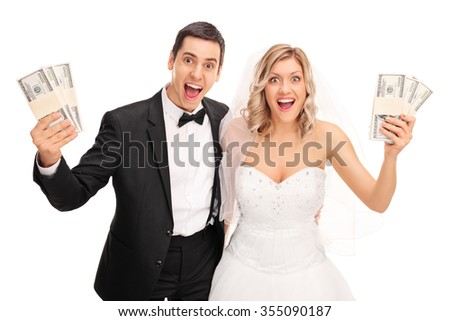 Happy newlywed couple holding few stacks of money and looking at the camera isolated on white background - stock photo