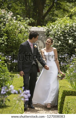 Happy newlywed couple looking at each other while holding hands other in the park - stock photo