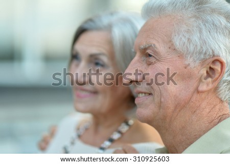 Happy nice mature couple walking in town - stock photo