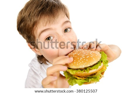 Happy nine year old boy  eating burger with appetite. Fast food. Concept of healthy and unhealthy food. Isolated over white. - stock photo