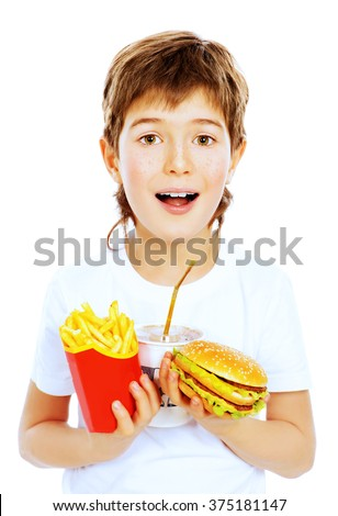 Happy nine year old boy holds french fries, burger and soda and smiling. Fast food. Concept of healthy and unhealthy food. Isolated over white. - stock photo