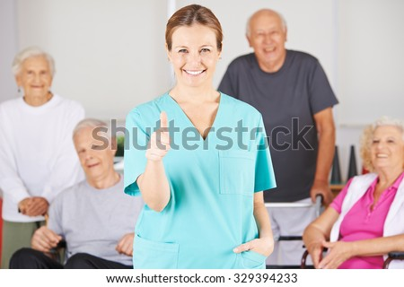 Happy nursing assistant holding her thumbs up in front of a happy group of senior people - stock photo