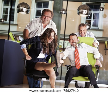 Happy office employees having fun at work in an office chair race. - stock photo