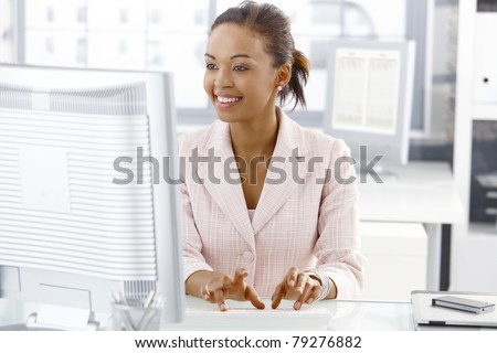 Happy office worker girl sitting at desk, working on computer, looking at screen.? - stock photo