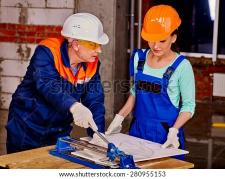 Happy old  builder man cutting ceramic tile. - stock photo