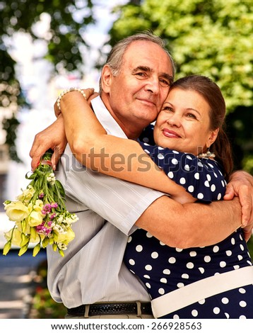 Happy old couple at summer  outdoor. Elderly people hugging - stock photo