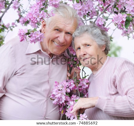 happy old couple on the flowering  apple-tree  background - stock photo