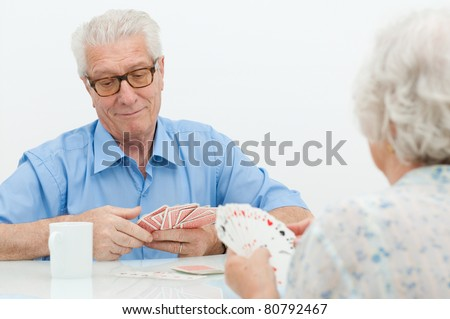 Happy old couple playing together with  cards at home - stock photo