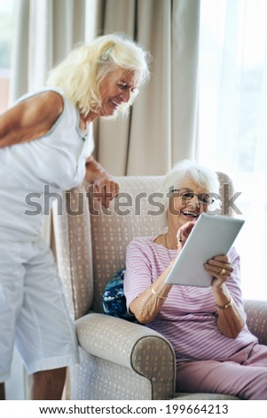 Happy old female friends laughing together and looking at touchscreen - stock photo