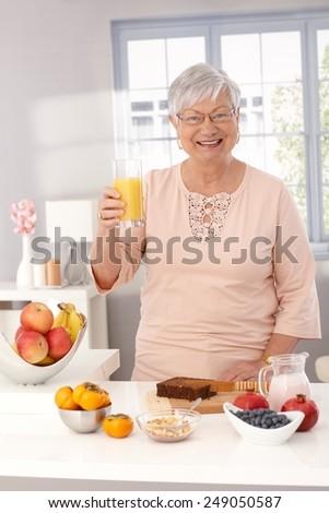 Happy old lady drinking orange juice, preparing healthy breakfast, smiling, looking at camera. - stock photo