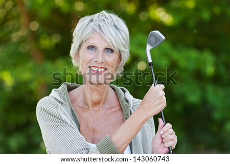 Happy old lady holding the golf stick standing in the golf club. - stock photo