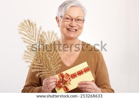 Happy old lady with golden fan and present at christmas, smiling. - stock photo