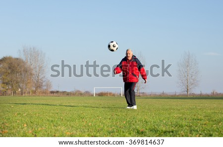 Happy old man in seventies kicking a soccer ball on the grass field - stock photo