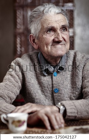Happy old man indoor having his morning cup of coffee - stock photo