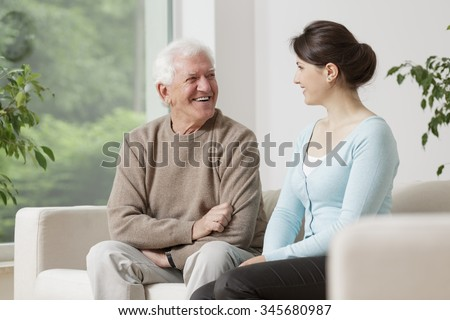 Happy old man smiling to young woman - stock photo