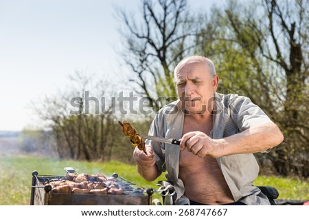 Happy Old Man with Open Shirt and Sitting on his Wheelchair Checking the Grilled Meat on Stick Using Knife to Know if Properly Cooked. - stock photo