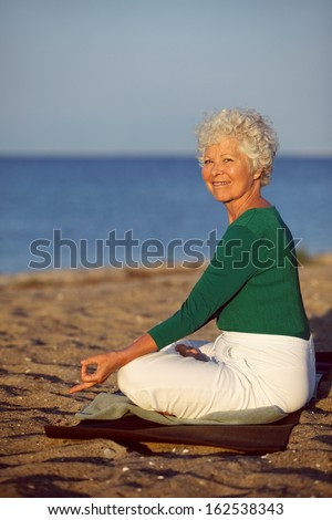 Happy old woman going relaxation exercise while sitting on sandy beach. Senior caucasian practicing yoga by the ocean in morning. Meditation, yoga and relaxation concept. - stock photo