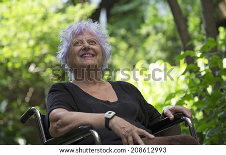 happy old woman on a wheelchair - stock photo