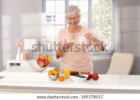Happy old woman preparing healthy breakfast, pouring milk over cereals, smiling, looking at camera. - stock photo