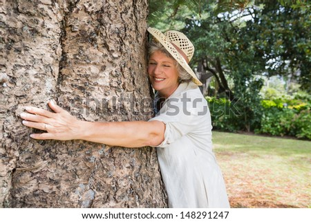 Happy older woman hugging a tree with closed eyes - stock photo