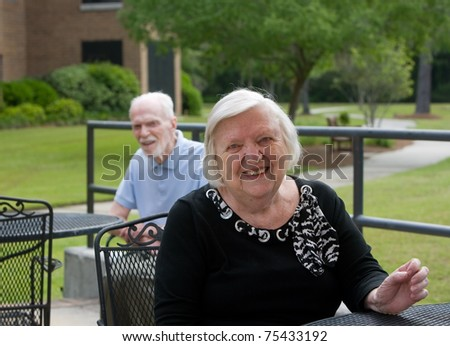 Happy older woman smiling while outside during day - stock photo