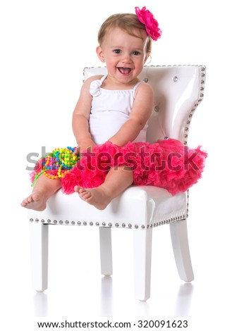 happy one year old girl wearing tutu sitting on a white chair - stock photo