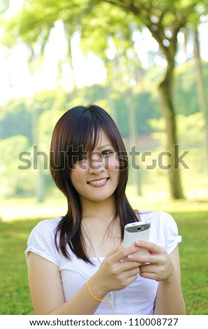 Happy oriental Asian young student using mobile phone to online / texting / sms , outdoor green park - stock photo