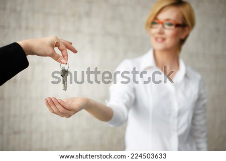 Happy owner passing keys from house in office, real estate - stock photo