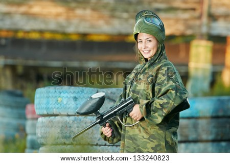 Happy paintball sport player girl in protective camouflage uniform and mask with marker gun outdoors - stock photo