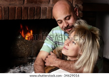 Happy pair near a fireplace in winter evening - stock photo